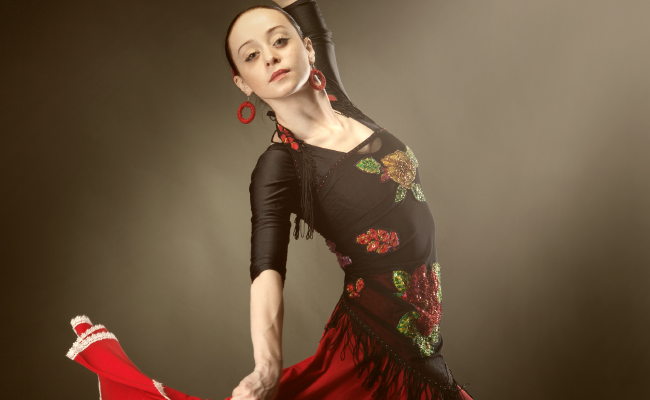 Flamenco dancer twirling in traditional gown in front of a dark background