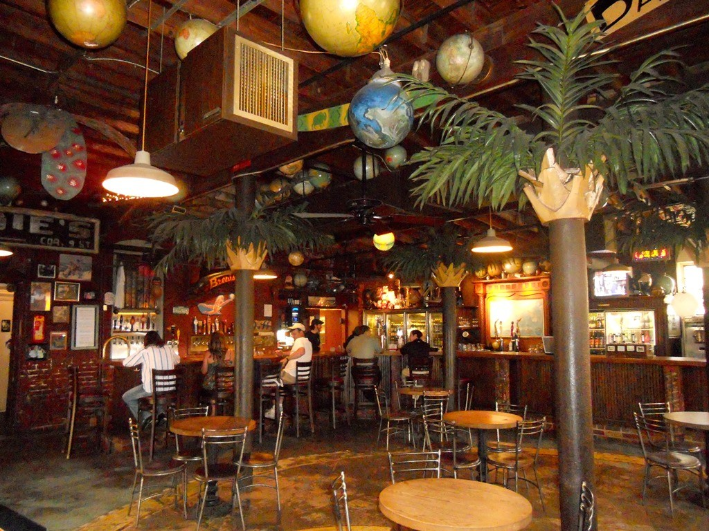 Dining room of New World Brewery features an indoor patio seeting, large bar and palm trees with globes suspended from the ceiling