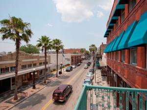 View of Ybor street from apartment balcony, looking down road seeing palm trees and cars driving into the distance