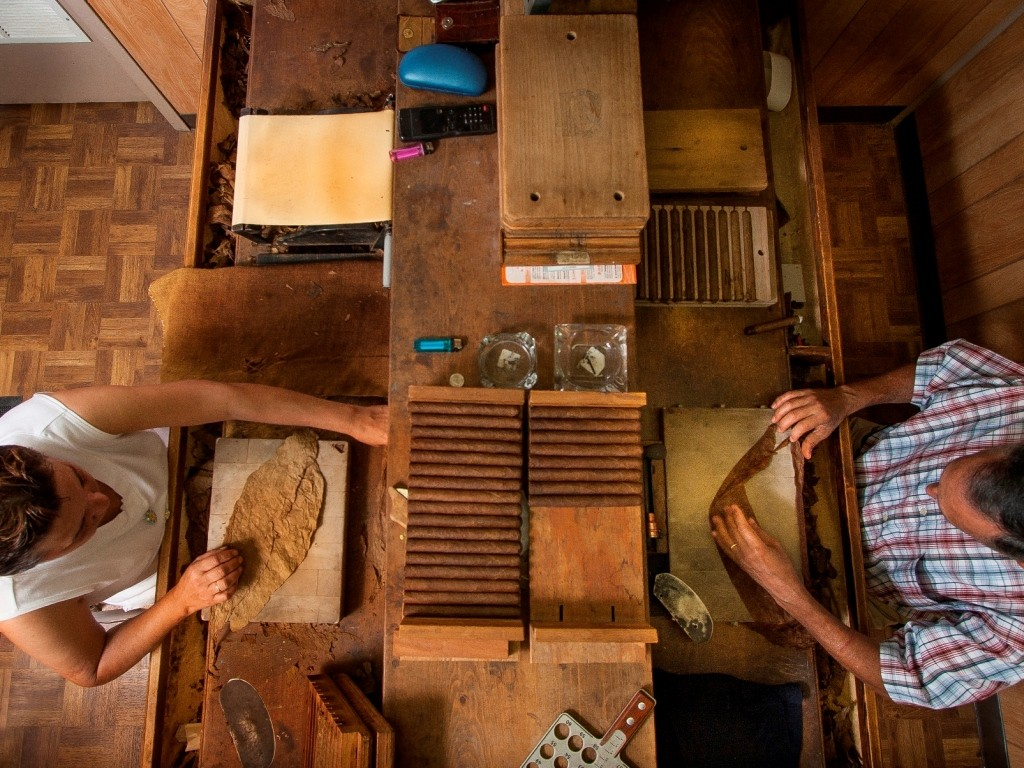 Aerial view of two workers rolling cigars