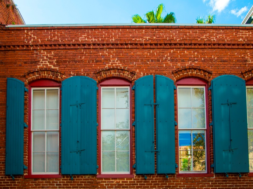 bright blue window shutters on a red brick building
