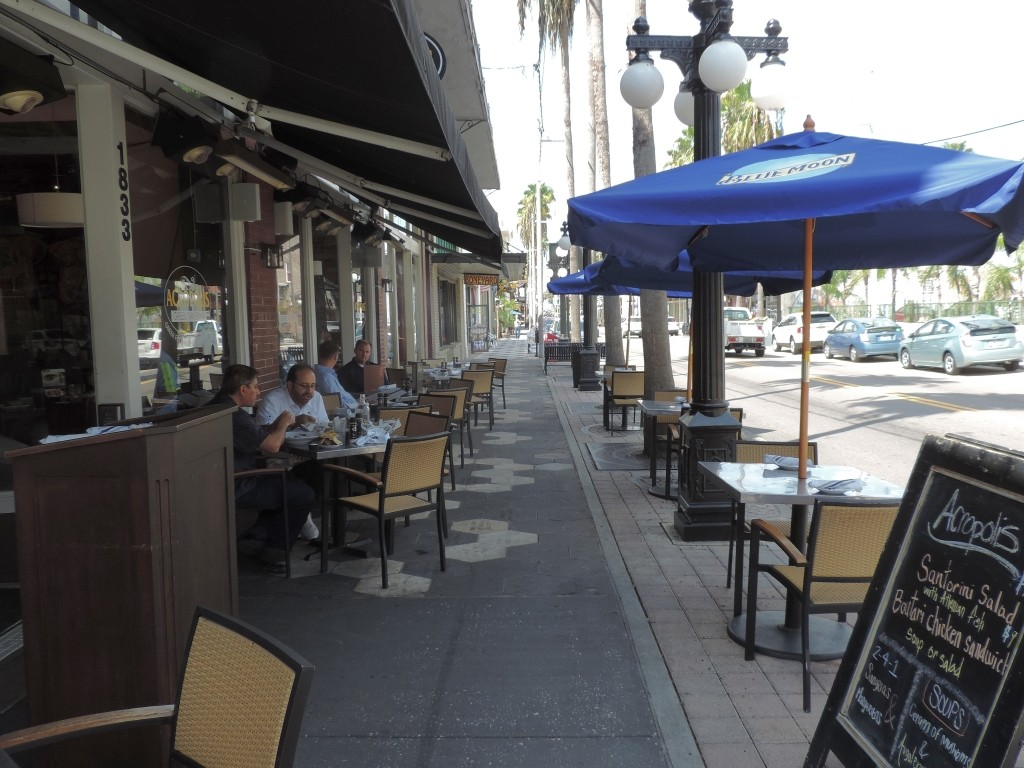 Outdoor sidewalk cafe with people enjoying lunch