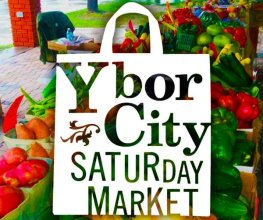 Ybor City Saturday Market Logo on white shopping bag over table full of vegetables