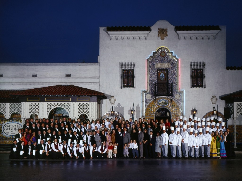 large group of restaurant employees from the Columbia Restaurant posed for 100th anniversary group photo in front of restaurant