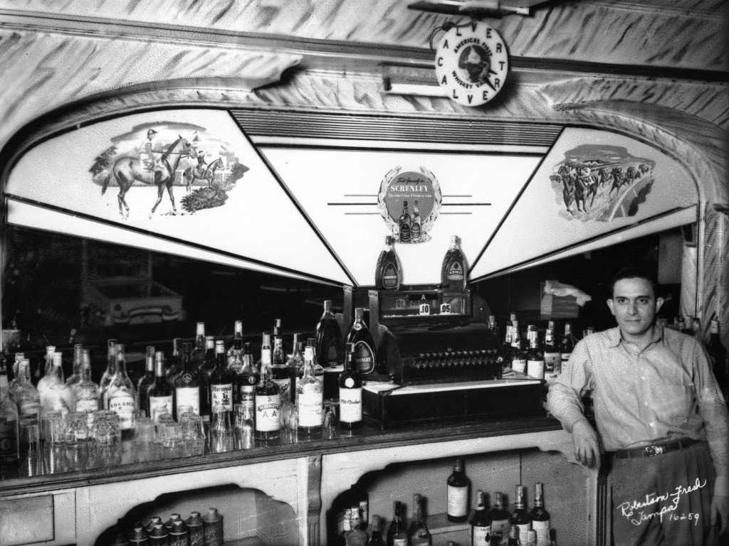 Classic photo of Bartender posing in front of bottles of liquor