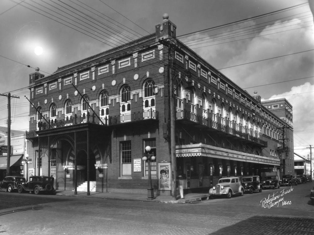 Historic photo of large two story brick building with classic cars parked along the side