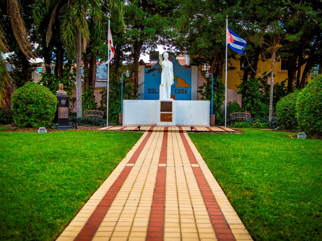 Statue at Jose Marti Park between a Florida and a Cuban Flag at the end of a long brick walk way