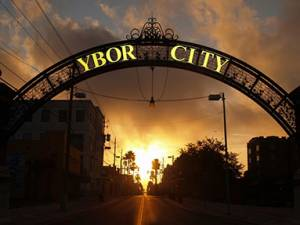 Metal Archway over avenue entrance with words Ybor City shining behind the sun rising in the distance