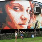 girls jumping in front of a mural