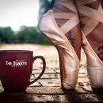 close up of ballerina toe point next to coffee cup