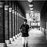kid with backpack walking on sidewalk