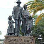Bronze statue of immigrant family in park