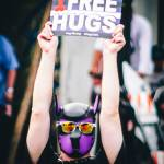 "Man wearing dog mask holding sign ""Free Hugs"""