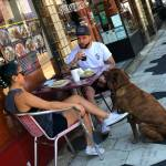 Man and woman with dog eating at table outside of restaurant