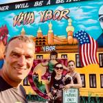 "man posing in front of ""Viva Ybor"" mural"